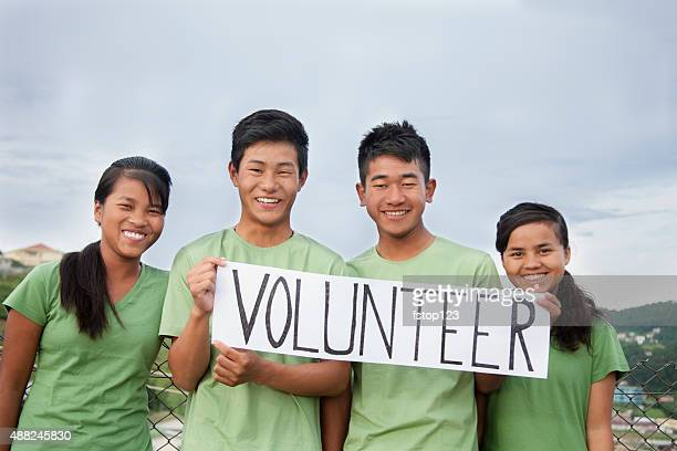 Multi-ethnic group of teenagers hold 'volunteer' sign outdoors.