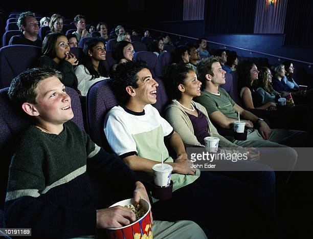 Multi-ethnic group of teens (17-19) watching movie in theater