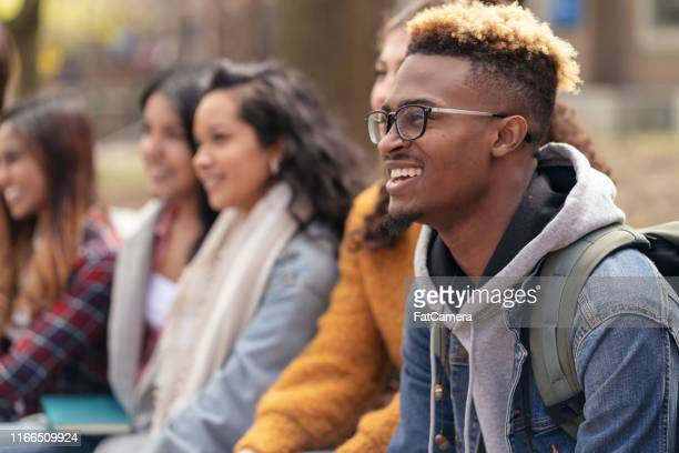 multi-ethnic group of university students relaxing outside - college students stock pictures, royalty-free photos & images