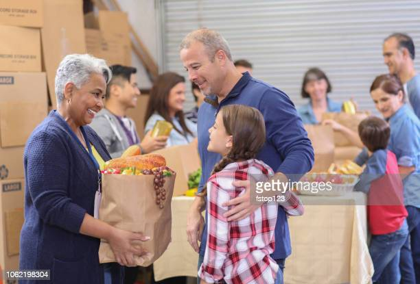 multi-ethnic group of volunteers work at food bank. - hungry stock pictures, royalty-free photos & images