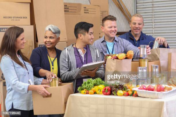 multi-ethnic group of volunteers work at food bank. - food drive stock pictures, royalty-free photos & images