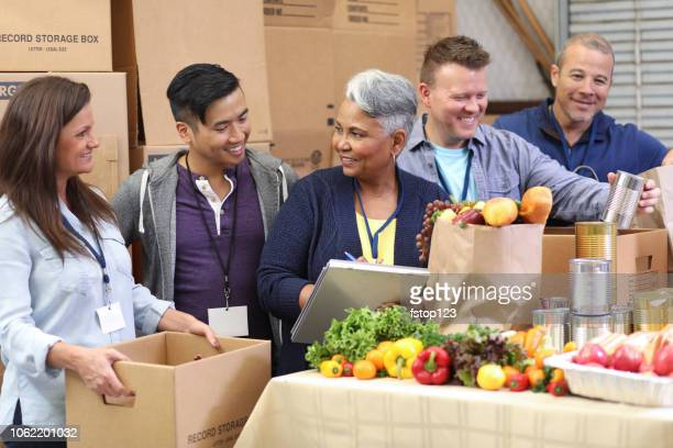 multi-ethnic group of volunteers work at food bank. - non profit organization stock pictures, royalty-free photos & images