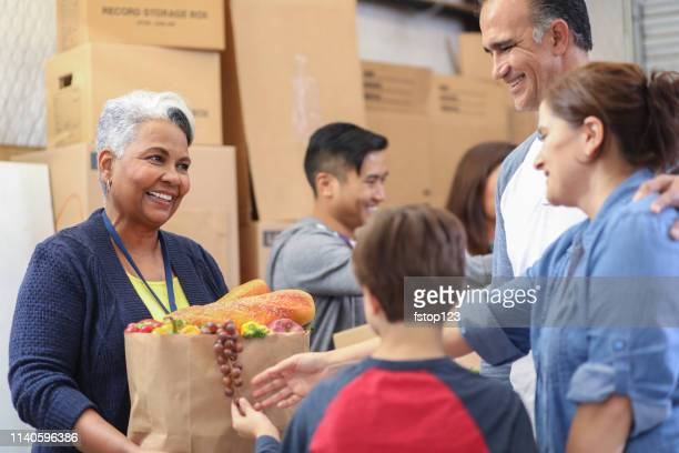 multi-ethnic group of volunteers work at food bank. - food pantry stock pictures, royalty-free photos & images