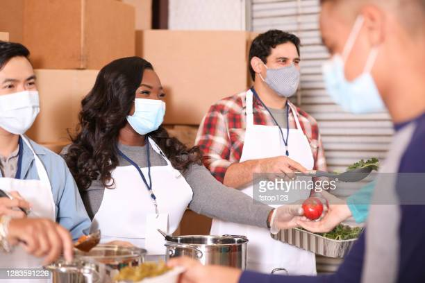 multi-ethnic group of volunteers work at soup kitchen. - giving tuesday stock pictures, royalty-free photos & images