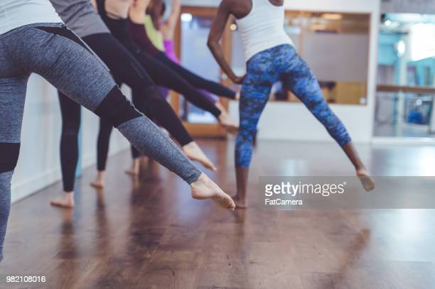 multiethnic group of women do a barre workout together in a modern health club - barre stock photos and pictures