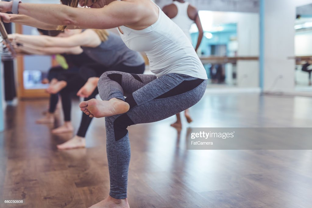 Multi-ethnic group of women doing barre workout : Stock Photo