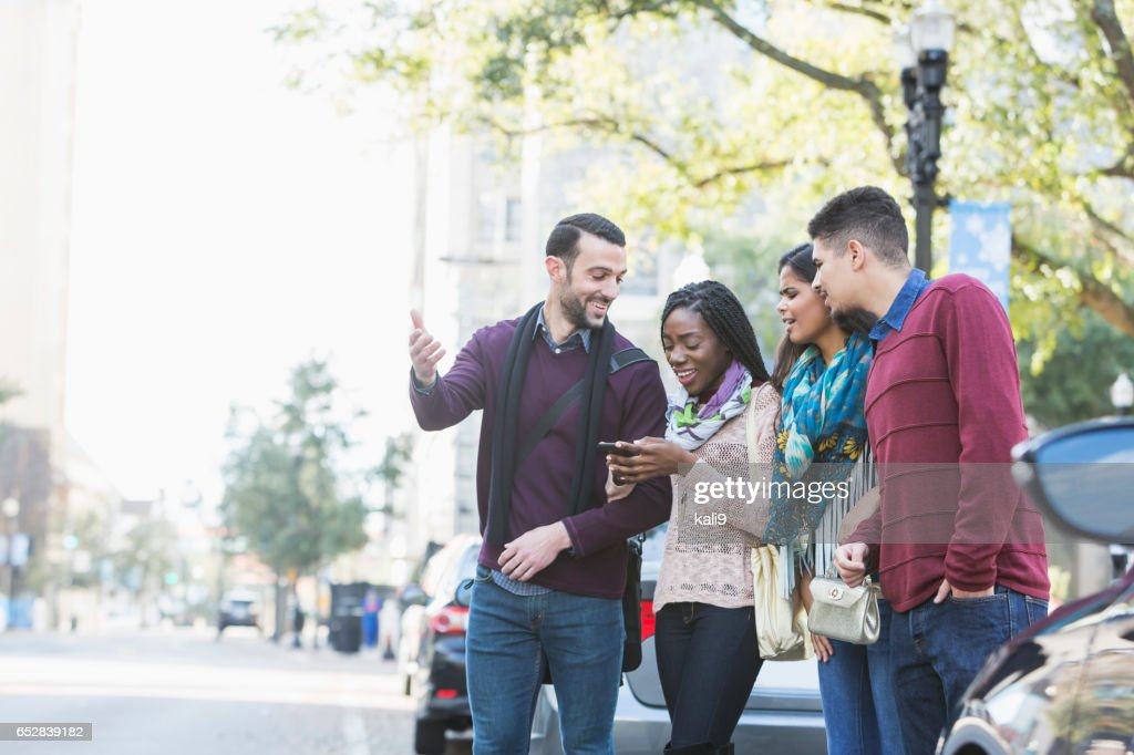 Multietnisk grupp unga vuxna väntar ride : Bildbanksbilder