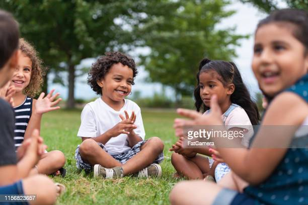 a multi-ethnic group of young children are clapping outside - children only stock pictures, royalty-free photos & images