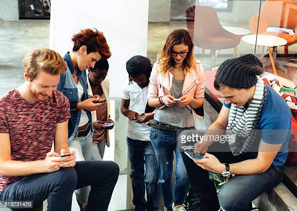 Multi-ethnic Group of Young People using their smart phones.