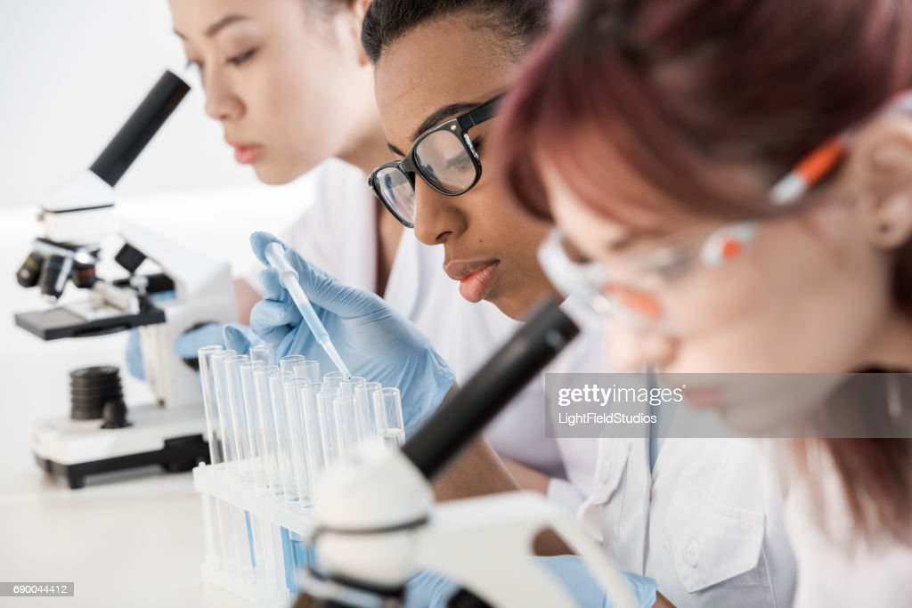 Multiethnic group of young professional scientists working with microscopes in chemical lab : Stock Photo