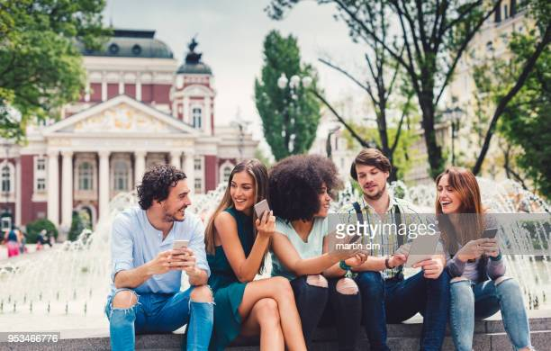 multi-ethnic group outside using modern technologies - clique stock photos and pictures