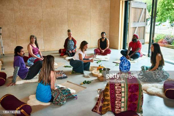 multi-ethnic group participating in tea ceremony during yoga class - buddhism stock pictures, royalty-free photos & images