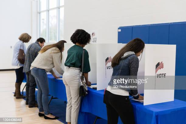 multi-ethnic group votes at voting booths - election voting stock pictures, royalty-free photos & images