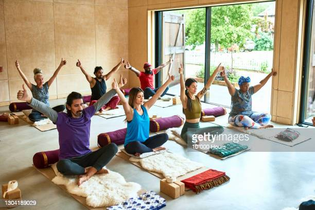 multi-ethnic group with arms raised during yoga session - limb body part stock pictures, royalty-free photos & images