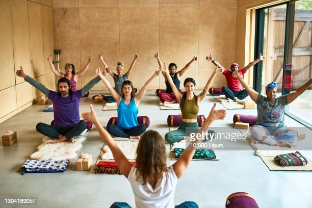 multi-ethnic group with arms raised in yoga studio - limb body part stock pictures, royalty-free photos & images