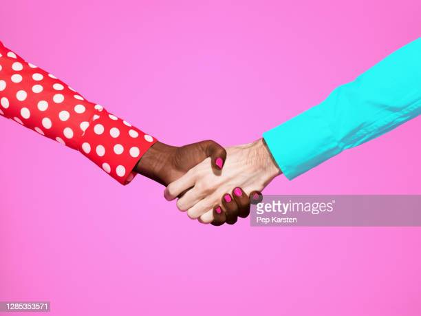 multiethnic handshake on pink background - printed sleeve stock pictures, royalty-free photos & images