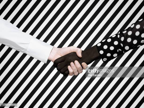 multiethnic handshake on striped background - printed sleeve stock pictures, royalty-free photos & images