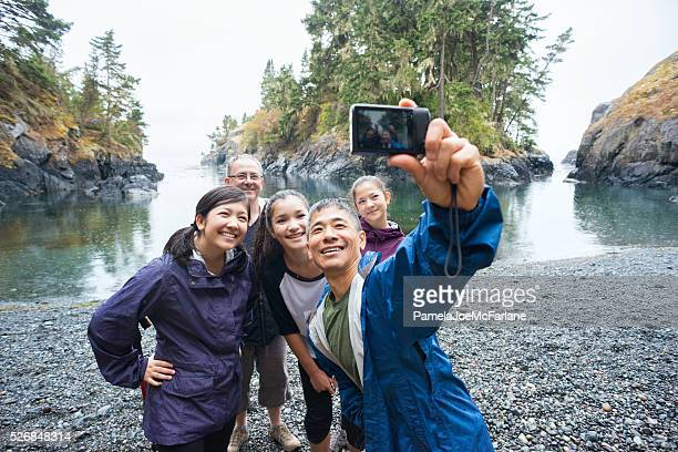 multi-ethnic hiking family posing for selfie on remote wilderness beach - moving activity stock pictures, royalty-free photos & images