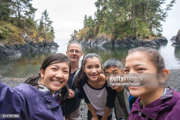 multi-ethnic randonnée famille posant pour selfie sur la plage sauvage robuste - ados lesbiennes en couple photos et images de collection