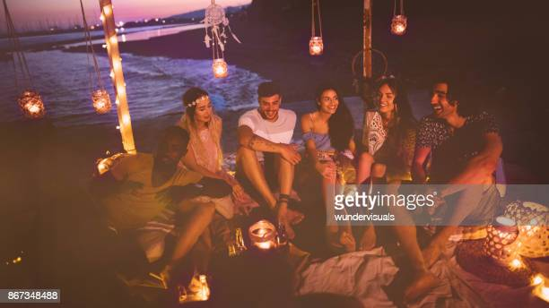 Multi-ethnic hipster couples having fun at summer night beach party
