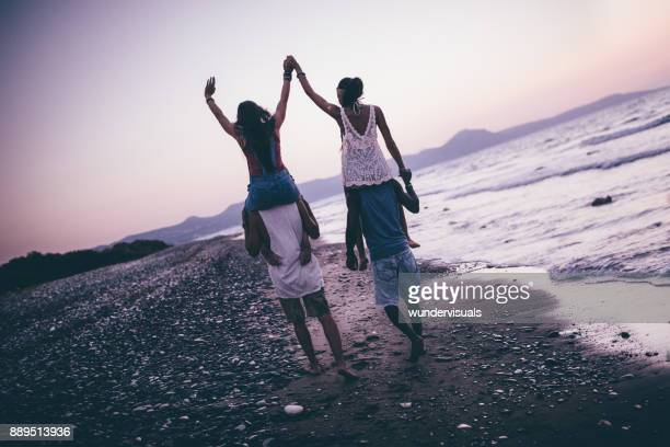 multi-ethnic hipster couples having fun with island beach piggy-back rides - carrying a person on shoulders stock photos and pictures