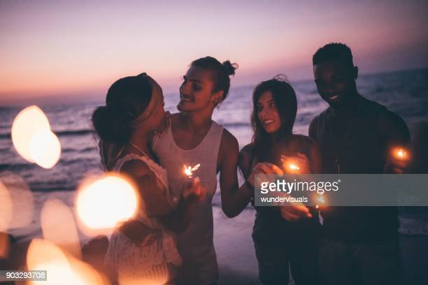 Multi-ethnic hipster friends and couples partying with sparklers at beach