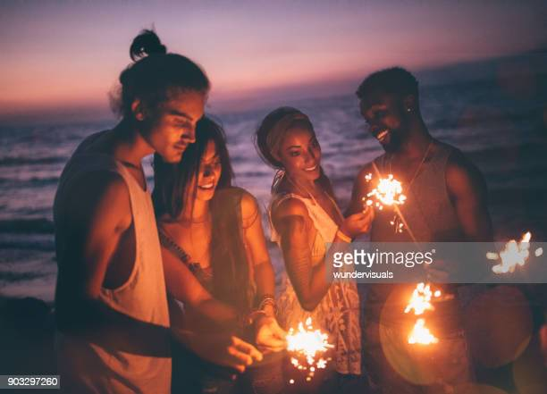 Multi-ethnic hipster friends celebrating with sparklers at beach party