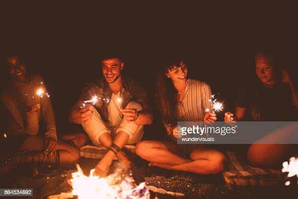 multi-ethnic hipster friends celebrating with sparklers sitting around beach campfire - camp fire stock photos and pictures
