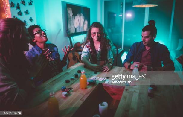 multi-ethnic hipster friends playing cards game at college dorm party - poker card game stock pictures, royalty-free photos & images