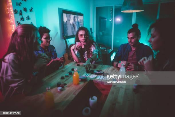 amigos de hipster multi-étnica jogando poker em casa - poker - fotografias e filmes do acervo
