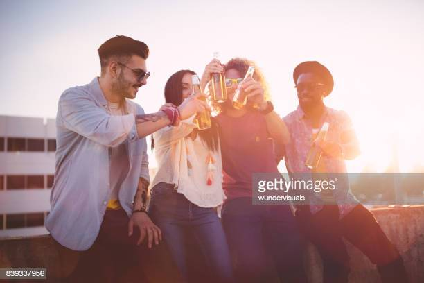 Multi-ethnic hipster friends toasting with beer at rooftop party