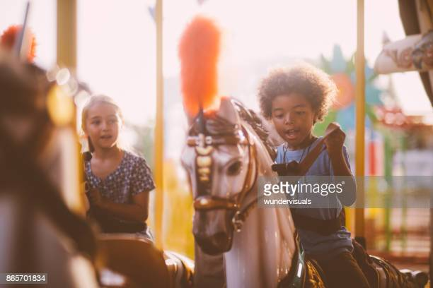 multi-ethnic kids having fun on amusement park merry-go-round ride - family photos stock photos and pictures