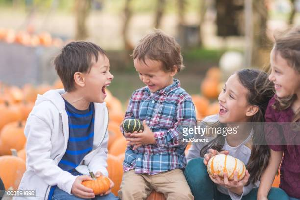 Multiethnic kids laugh together and pick out pumpkins on a farm