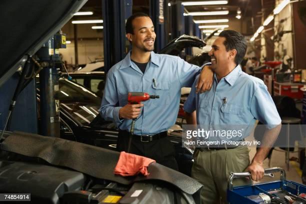 Multi-ethnic male auto mechanics in shop