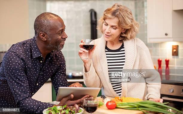 Multi-ethnic mature couple lookup recipe on tablet