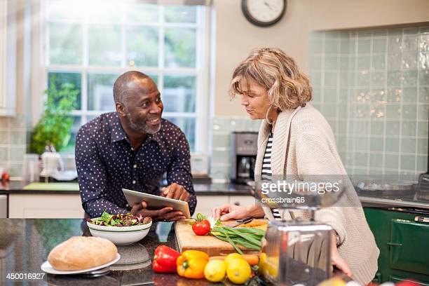 Multi-ethnic mature couple preparing food