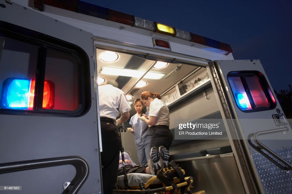 Multi-ethnic medical professionals with patient in ambulance : Stock Photo