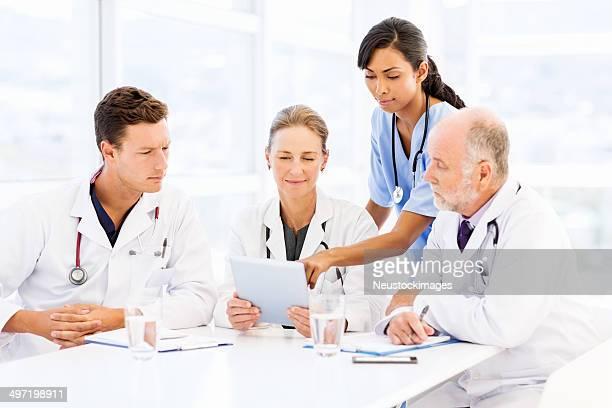 Multiethnic Medical Team Using Digital Tablet At Table