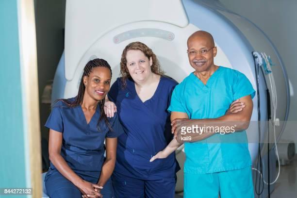 Multi-ethnic medical team with MRI scanner