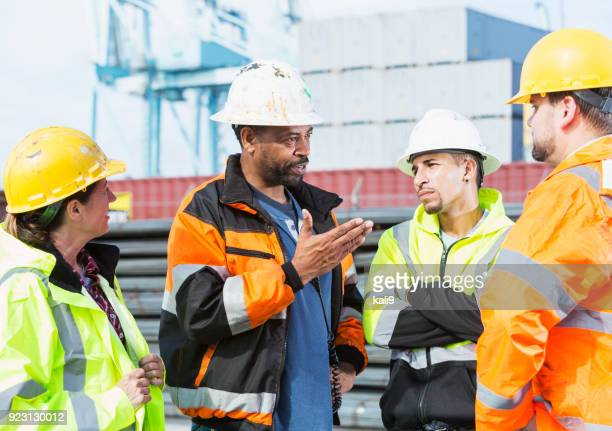 multi-ethnic men and woman working at shipping port - dock worker stock photos and pictures