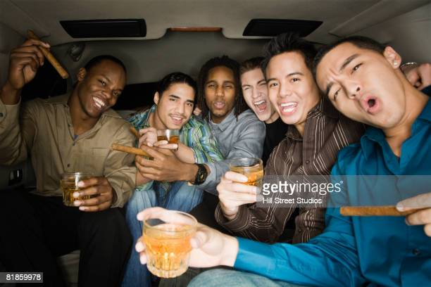 Multi-ethnic men celebrating in limousine