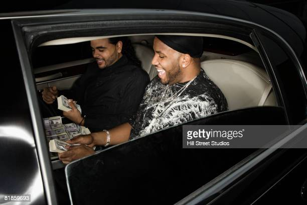 multi-ethnic men counting money in limousine - exceed and excel stock pictures, royalty-free photos & images