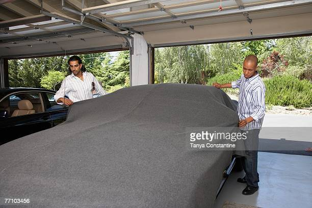 Multi-ethnic men covering car