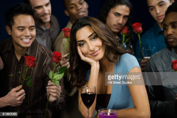 Multi-ethnic men giving roses to woman