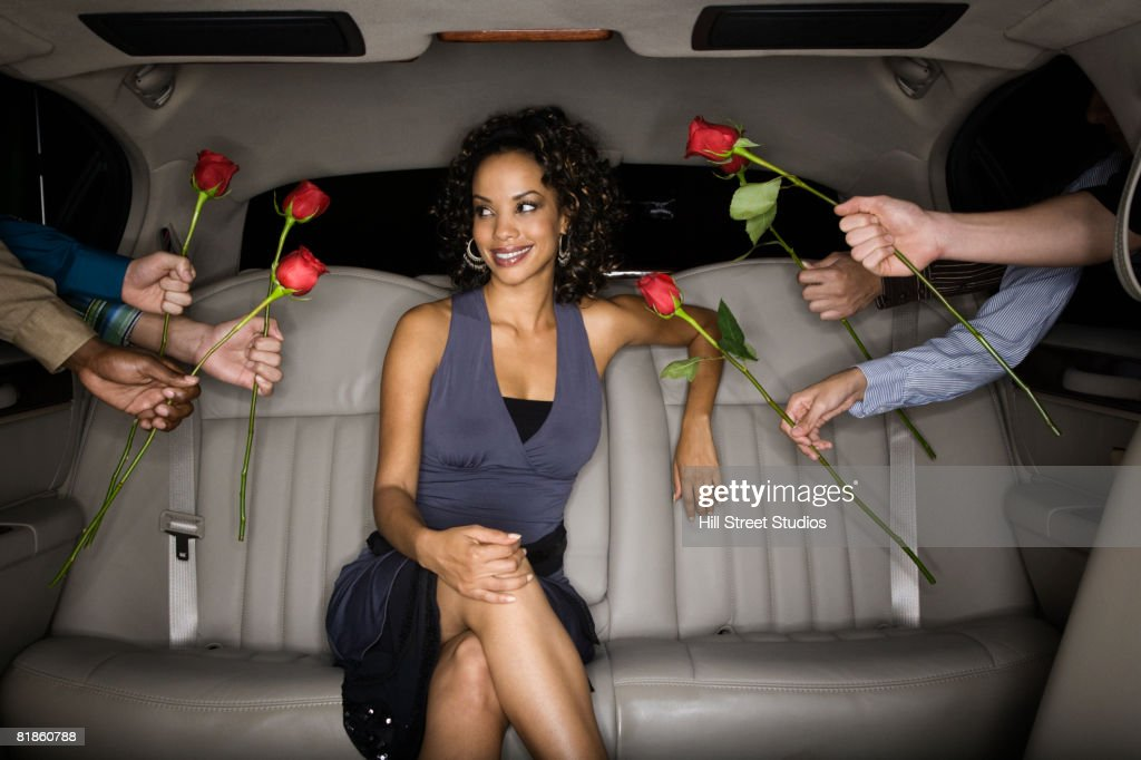 Multi-ethnic men handing roses to African woman in limousine : Stock Photo