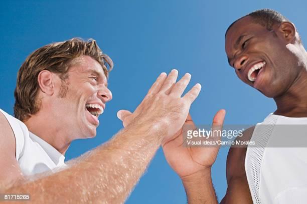 Multi-ethnic men high-fiving