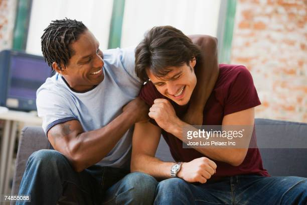 multi-ethnic men hugging on sofa - rough housing stock photos and pictures