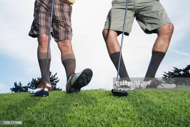 multi-ethnischen männer auf dem golfplatz ausdehnen - golf lustig stock-fotos und bilder