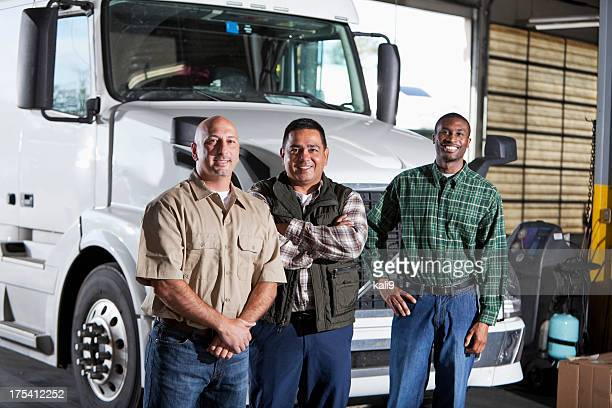 Multi-ethnic men standing next to semi-truck