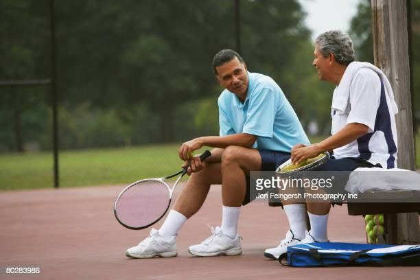 multi-ethnic men talking on tennis court - tênis esporte de raquete - fotografias e filmes do acervo